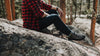 man sits on a rock at rocky mountain national park wearing so ill blue denim and approach shoes