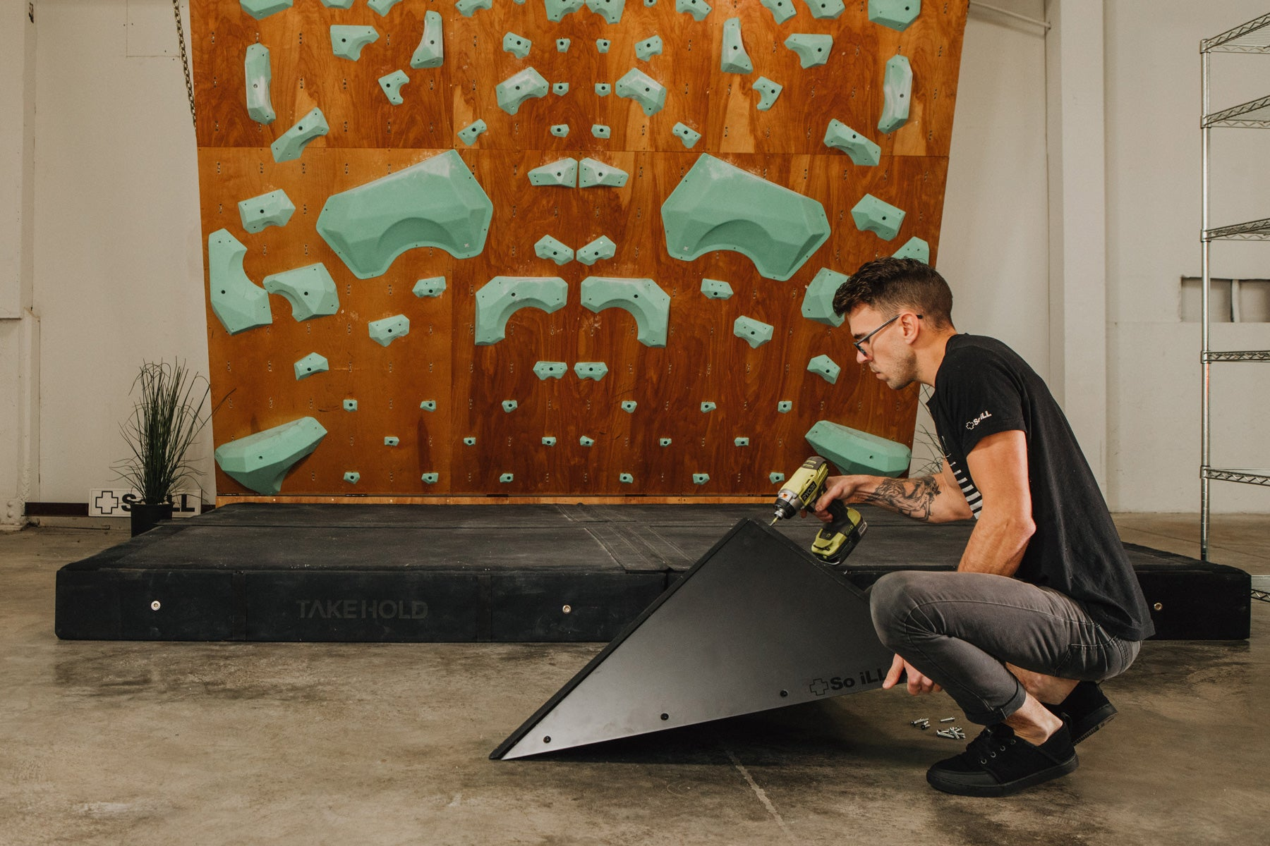 Routesetter John Oungst puts together a so ill flat pack volume in front of a climbing wall