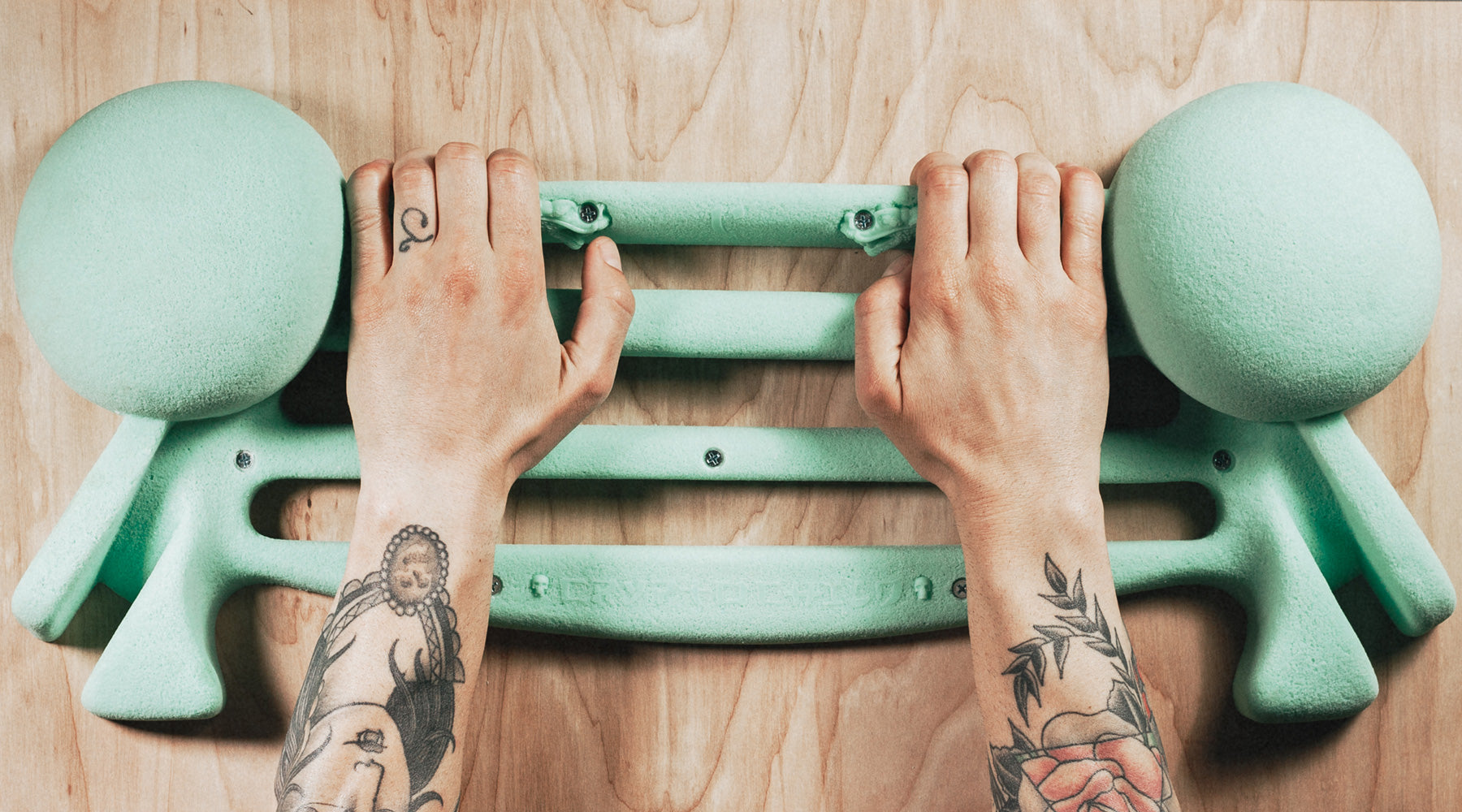 a man with tattoos trains on a seafoam so ill iron palm hang board