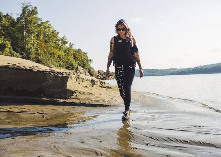 a lady walks on the beach wearing so ill repeat leggings