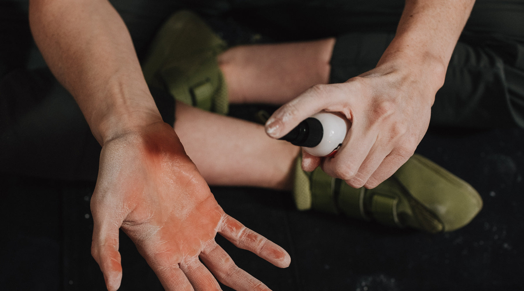 A climber sprays her hands with So iLL distribution Tokyo Powder React friction restorer