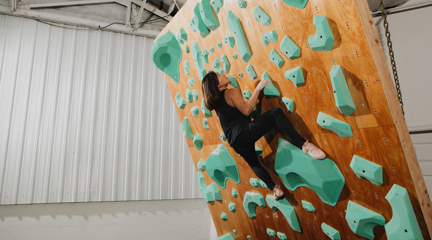 woman climbing on so ill climbing holds in so ill black denim while wearing On the Roam climbing shoes