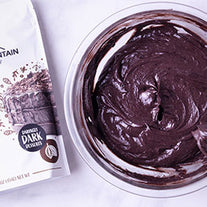 Black cocoa cream cheese frosting next to pouch of Modern Mountain black cocoa powder