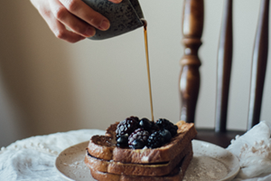 Syrup being poured over a stack of blueberry French toast