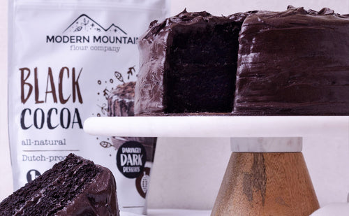 Black cocoa cake in front of pouch of Modern Mountain black cocoa powder