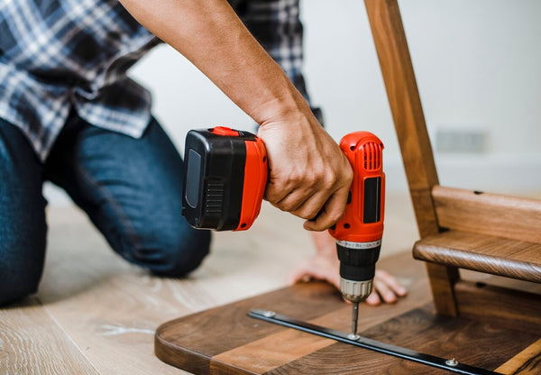 man using hand drill for table bolts and srews