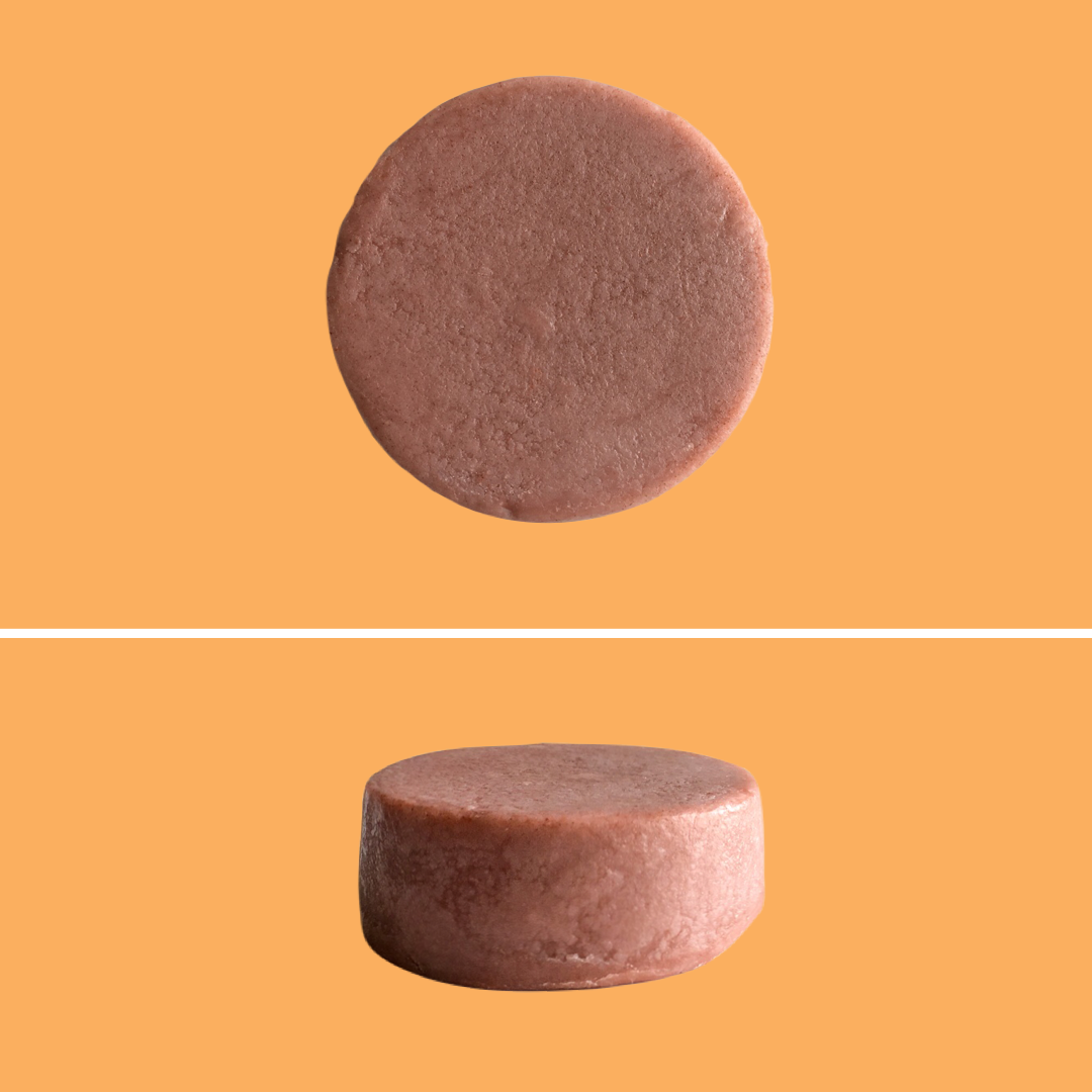 Top and side view of Green Ablutions Moroccan Argan Oil Conditioner Bar on orange background. Sustainable Zero-waste Plastic-free haircare.