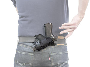 Man drawing gun from Advanced Back Holster