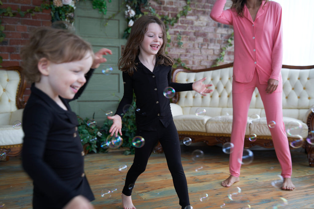 Kids in black Weekend Made pajama sets dancing with bubbles.