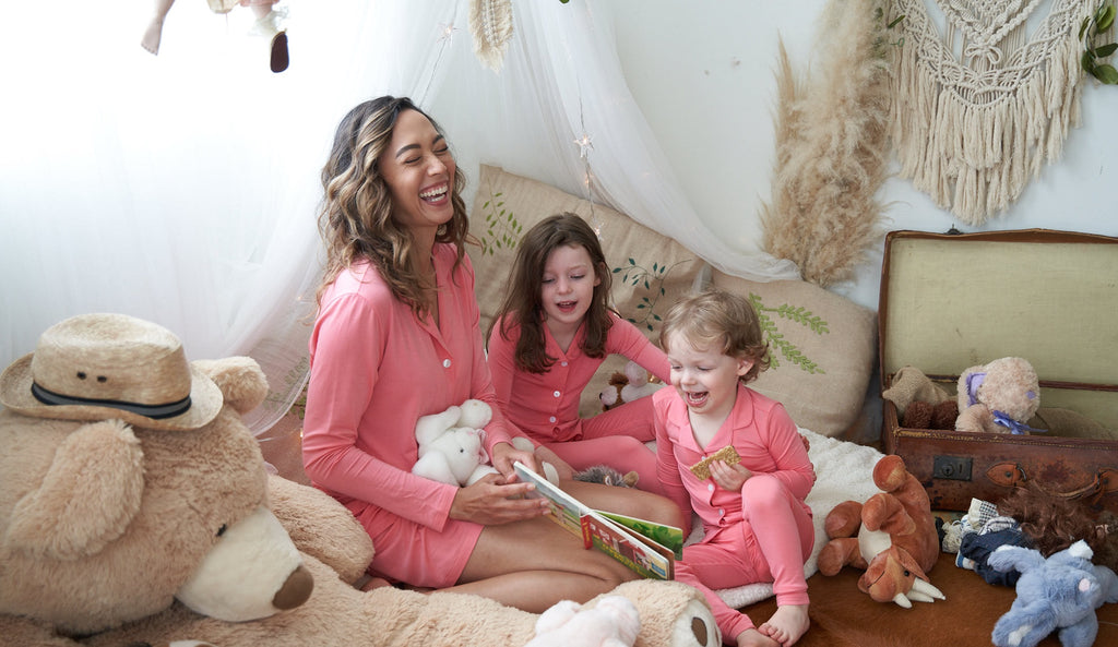 Family wearing blush beauty pink Weekend Made matching pajama sets while reading a book in the kid's reading nook.