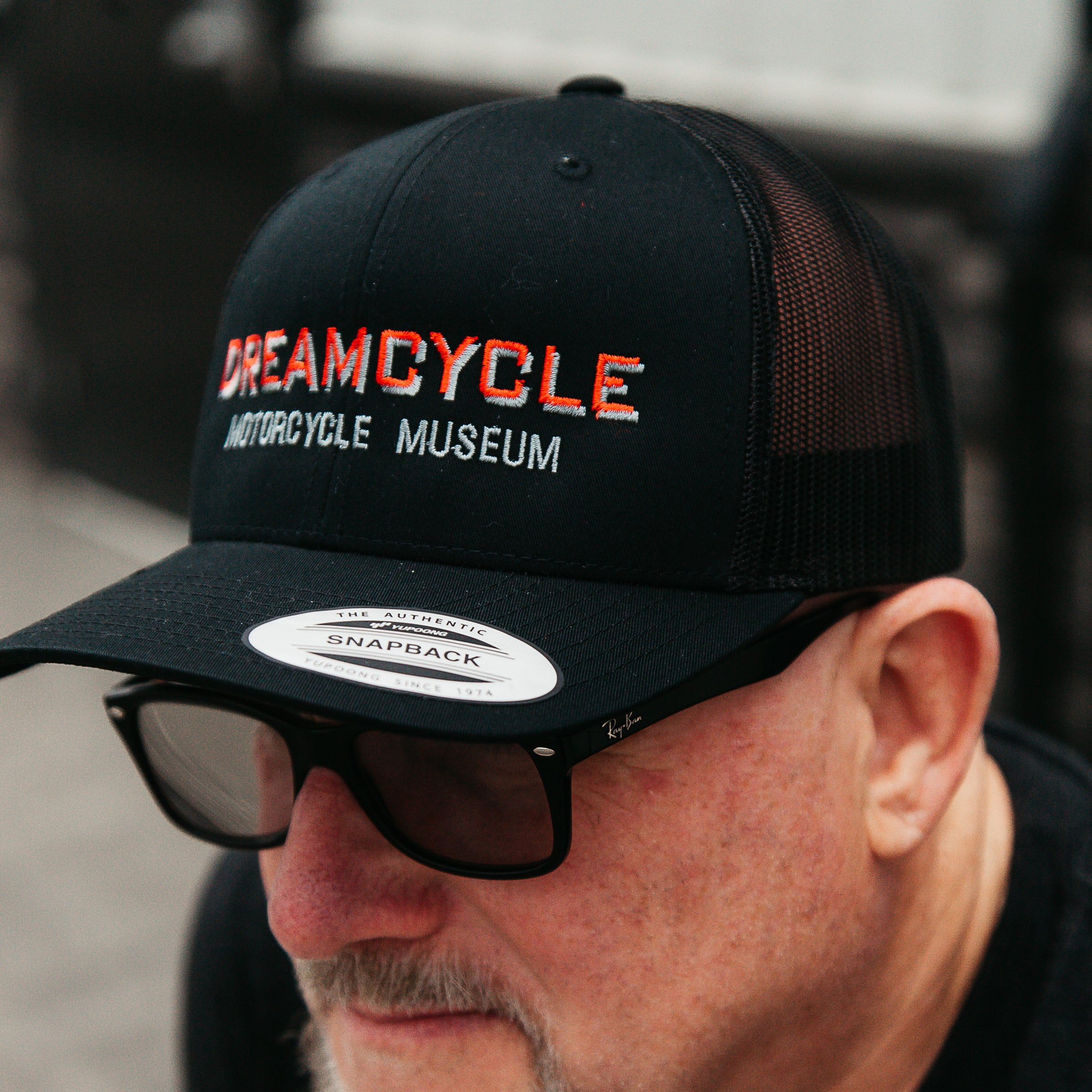 Dreamcycle Motorcycle Museum | Man wearing dreamcycle trucker hat in lifestyle setting.