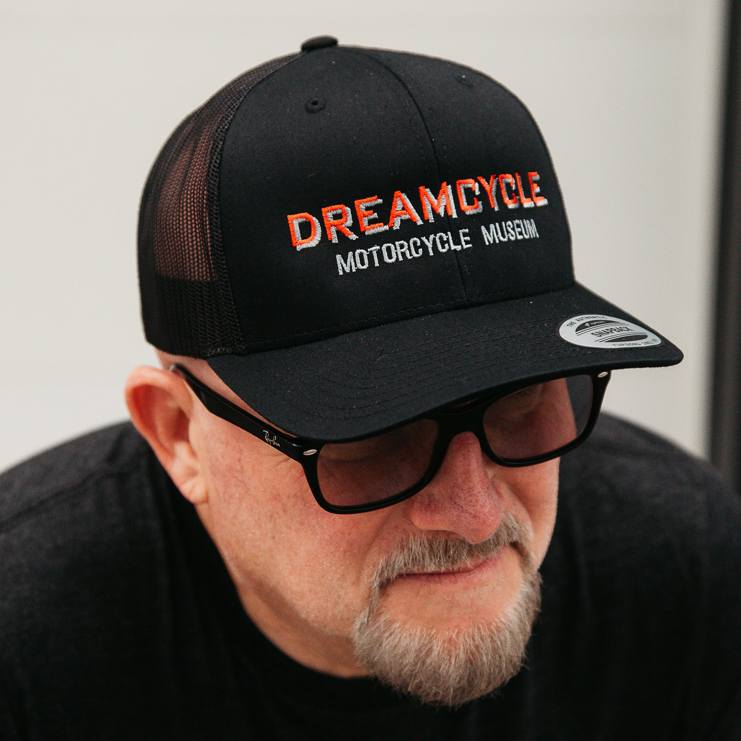 Dreamcycle Motorcycle Museum |  Man wearing Dreamcycle truckwr hat in lifestyle setting.