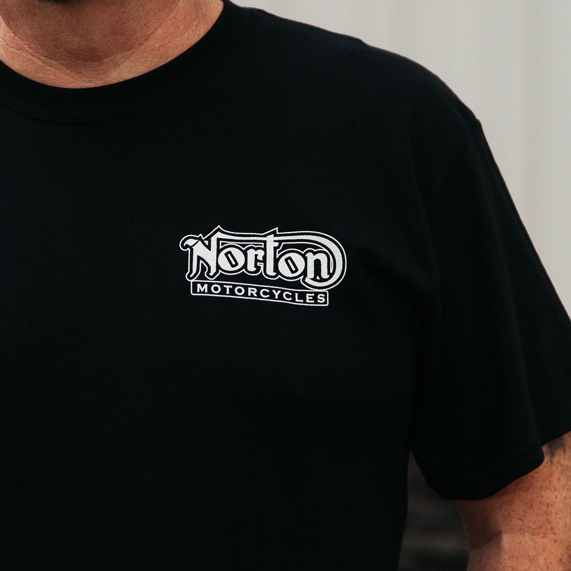 "Dreamcycle Motorcycle Museum |  Photo of mans shoulder wearing a black shirt with the text ""Norton motorcycles
