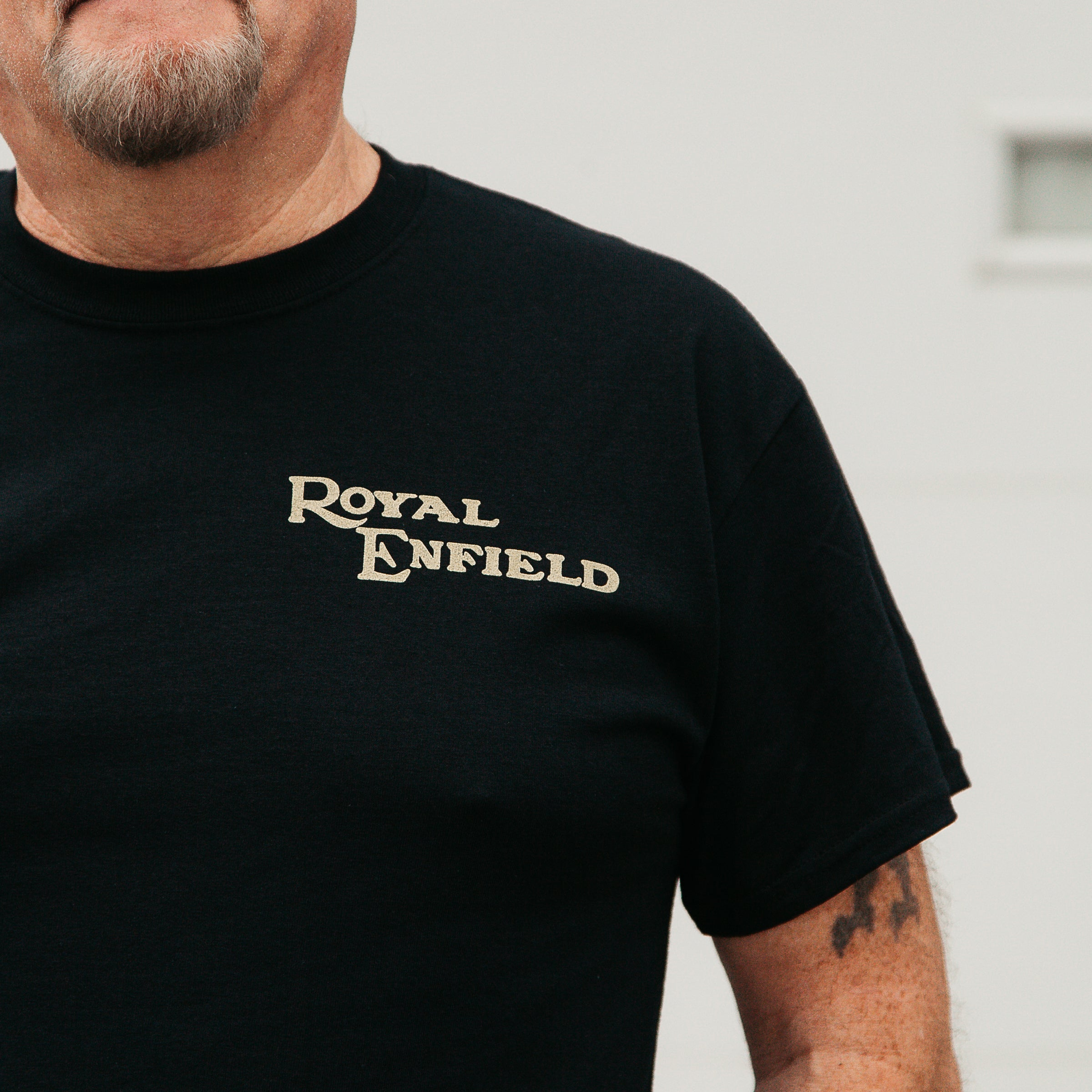 "Dreamcycle Motorcycle Museum |  Mans shoulder wearing black shirt with text ""Royal Enfield"" in lifestyle setting ."