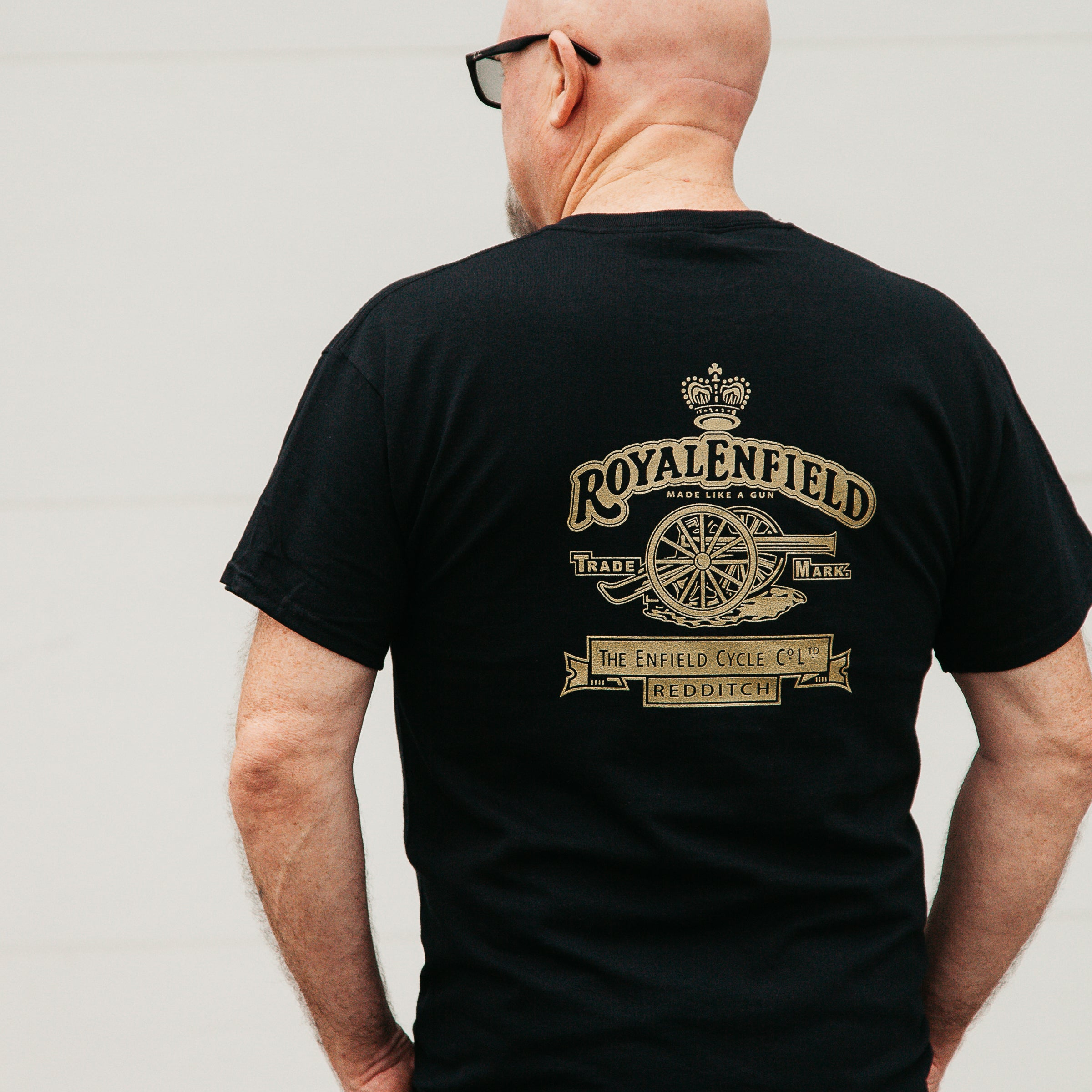 "Dreamcycle Motorcycle Museum |  Man wearing tshirt with text ""Royal Enfield"" Facing away from camera."