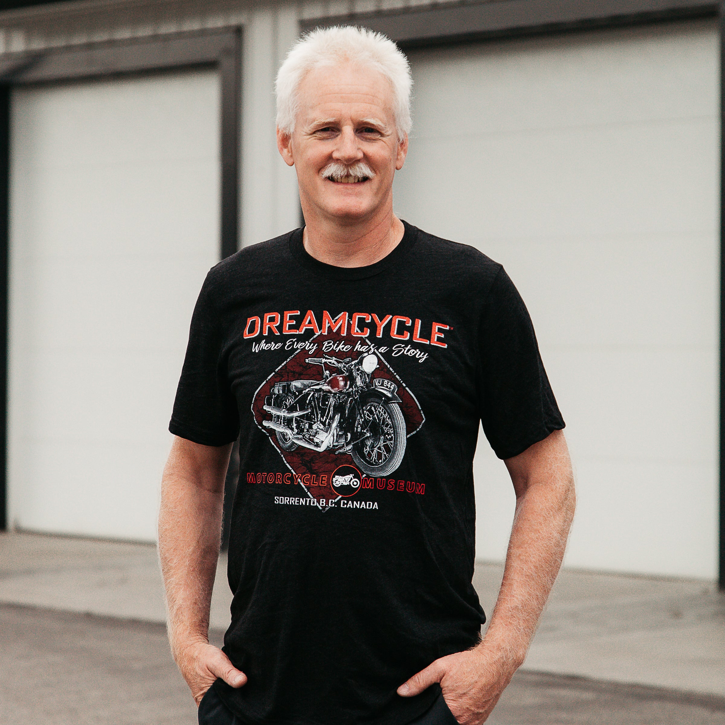 "Dreamcycle Motorcycle Museum |  Man posing in lifestyle setting wearing a tshirt that says ""Dreamcycle"" in bold letters with a motorcycle."