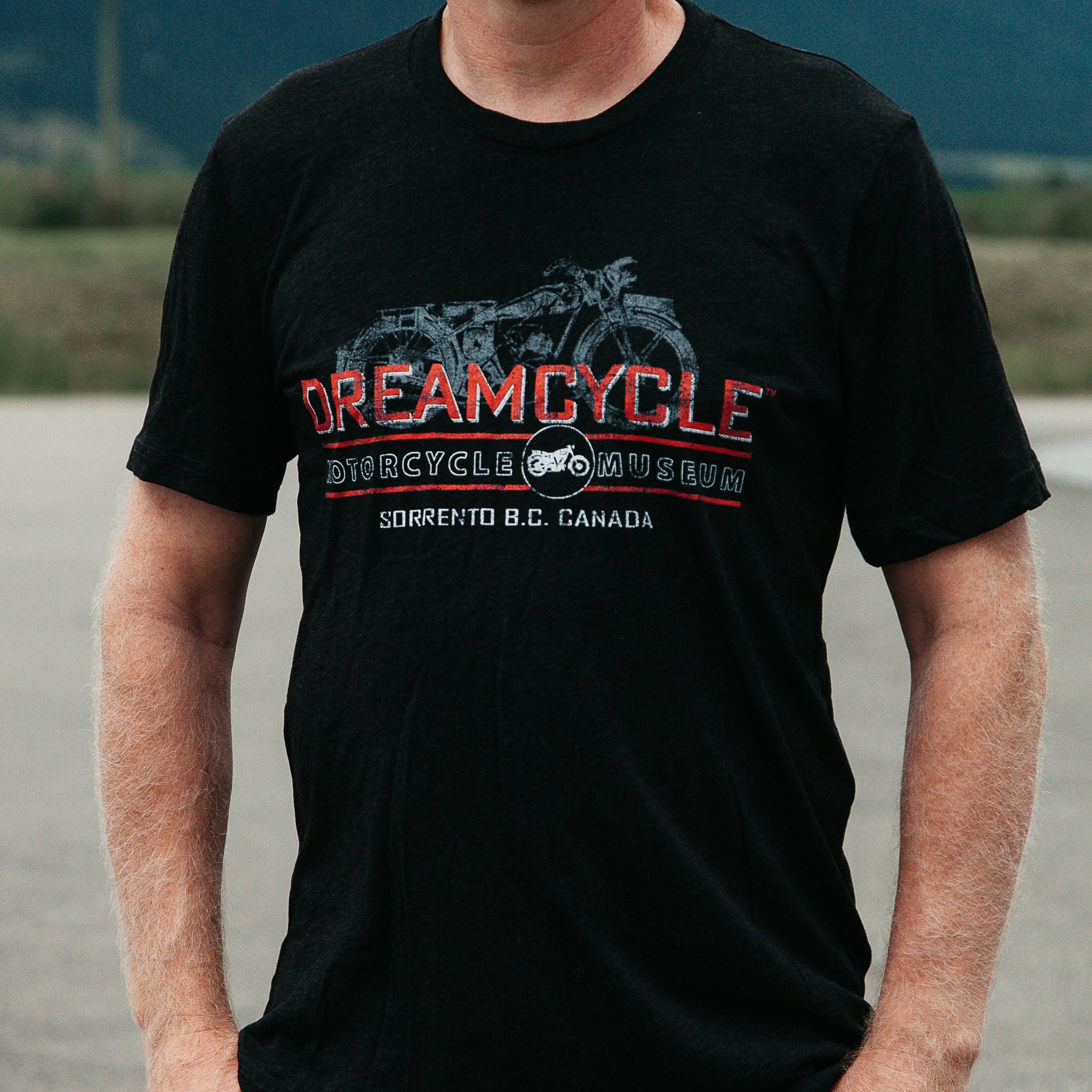 Dreamcycle Motorcycle Museum | Closeup man modeling dreamcycle tshirt with motorcycle.