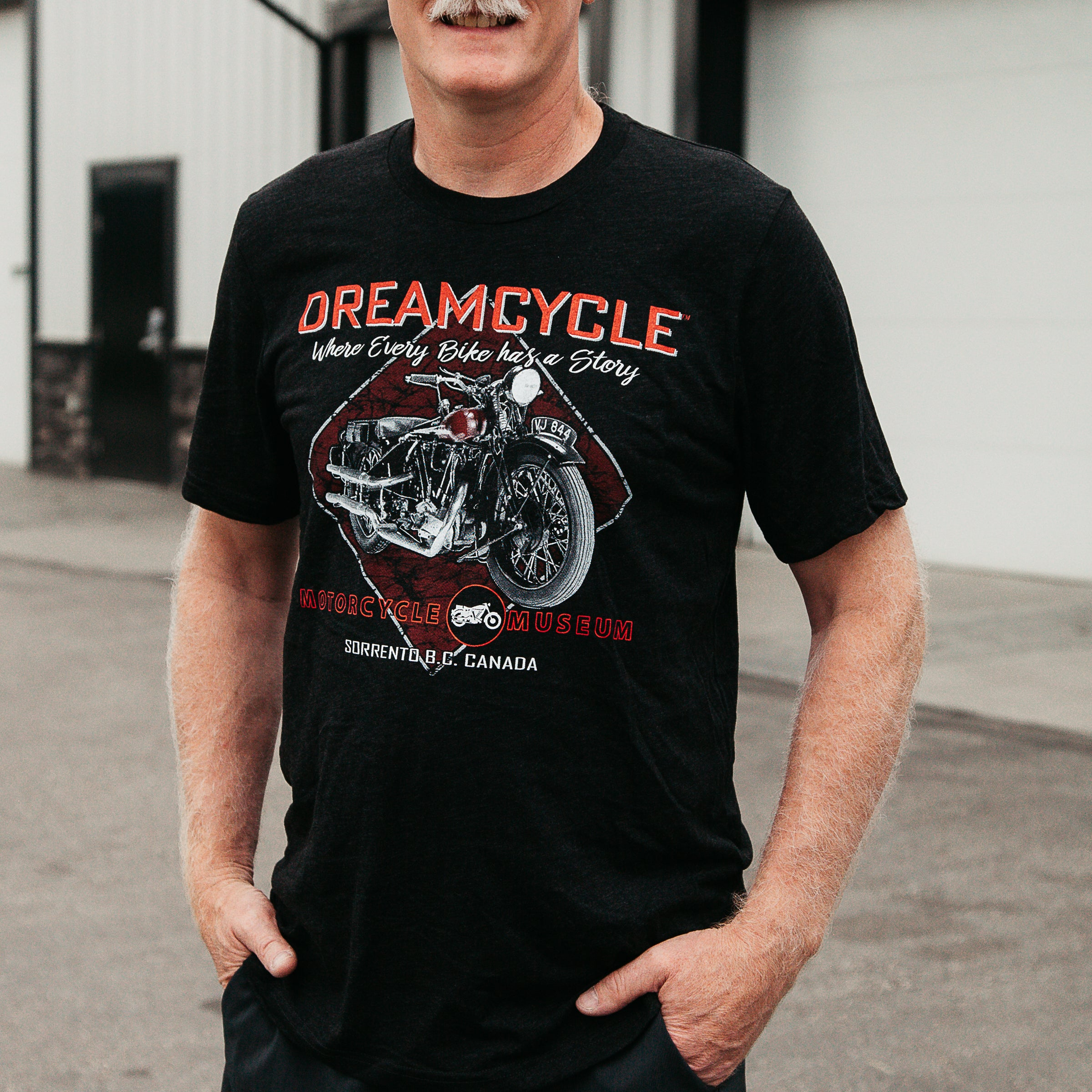 "Dreamcycle Motorcycle Museum |  Close up of a man standing in a lifestyle setting wearing a shirt that says ""`dreamcycle"" With a motorcycle on the front."