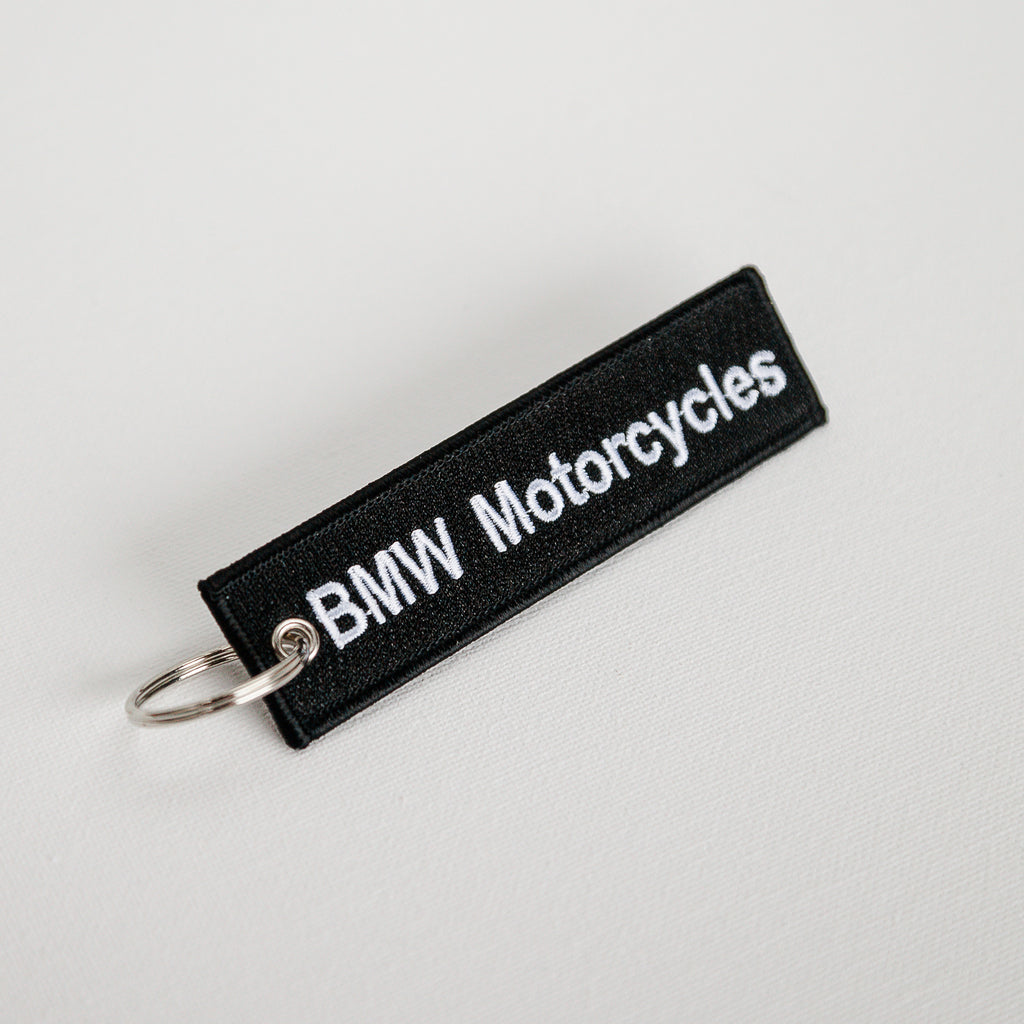 "Dreamcycle Motorcycle Museum |  Black Keychain with text ""BMW Motorcycles"" on White Background."