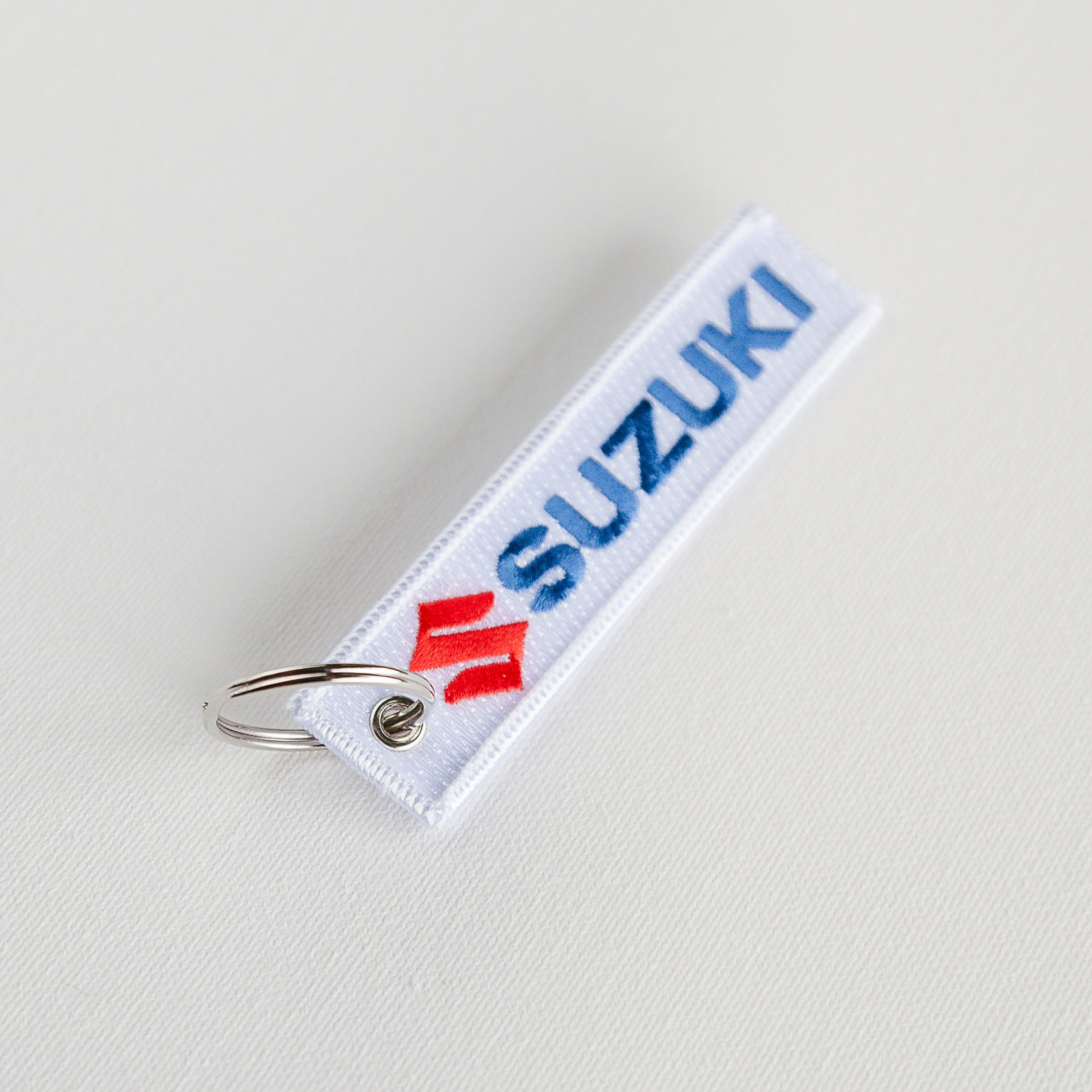 Dreamcycle Motorcycle Museum |  White suzuki keychain on white background.