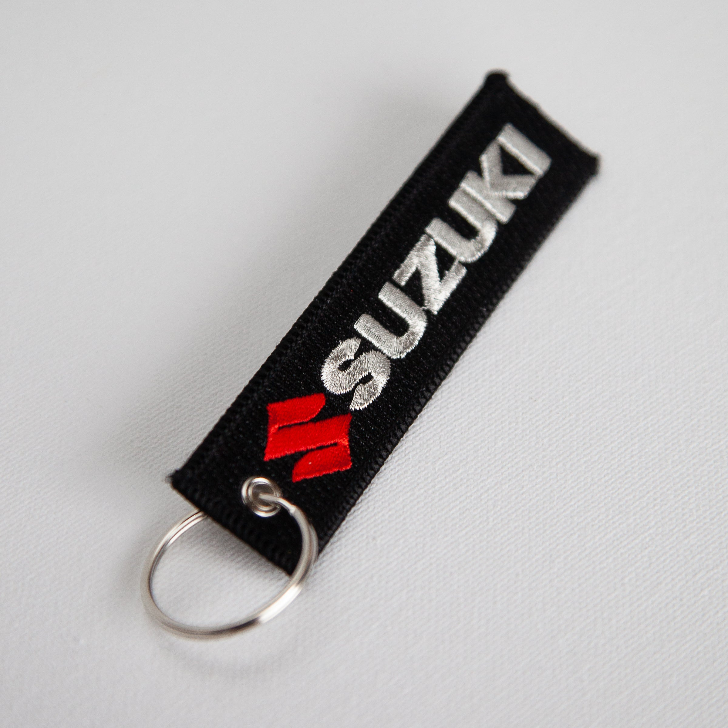 Dreamcycle Motorcycle Museum |  Black Suzuki keychain on white background.