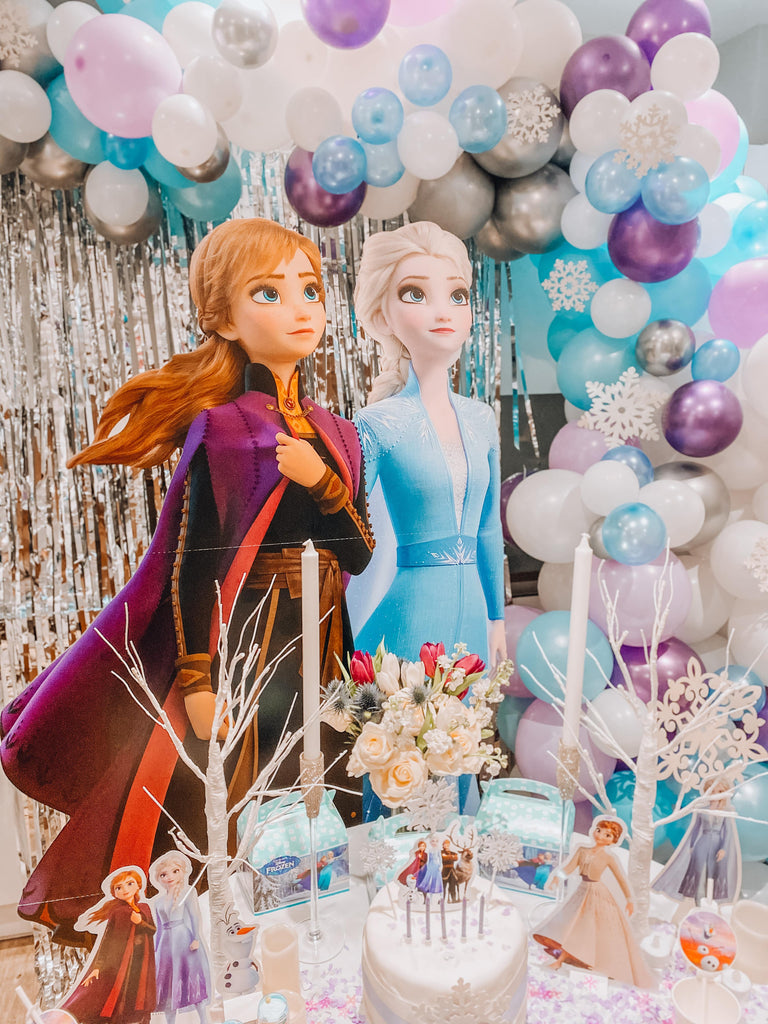 Disney Frozen themed kids birthday party dessert table, themed frozen balloons and ballon garland with themed tableware decorations.