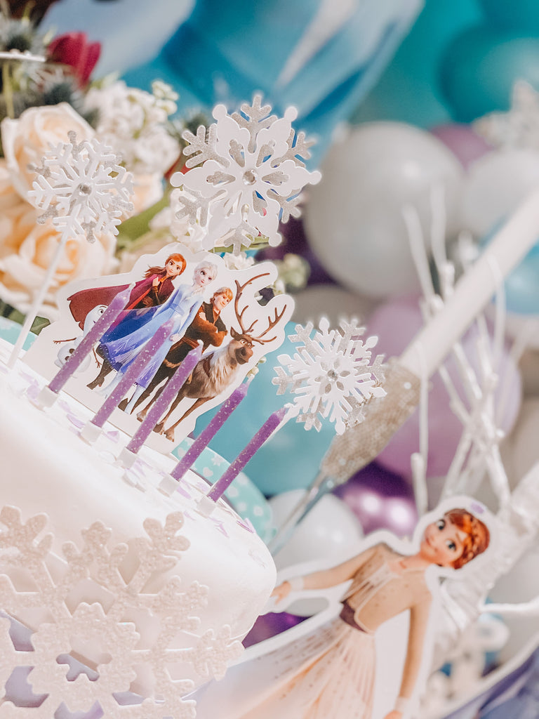 Disney Frozen themed kids birthday party birthday cake with Elsa, Anna and Olaf cake decorations and party tableware decor.