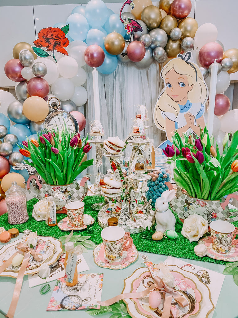 Alice in wonderland themed mad haters tea party decprations and party setup for kids birthday and themed events. Alice themed tableware and cutlery, eat me drink me, flowers, balloons, grass table runner.