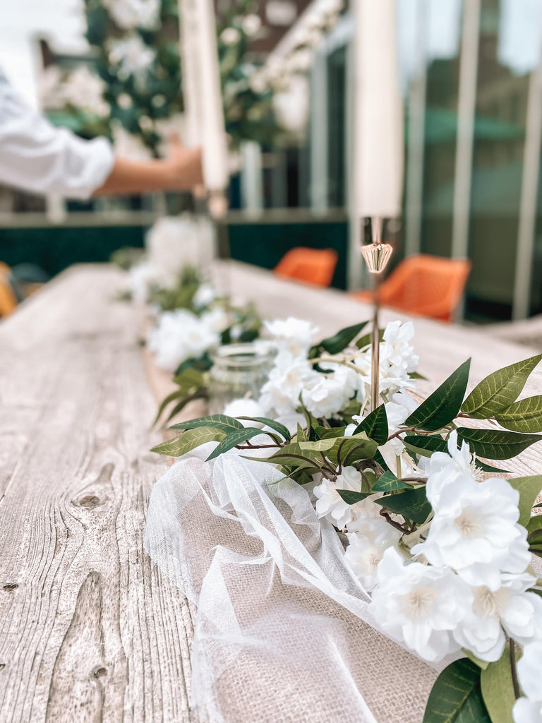 beautiful mixture of white and ivory flowers and luxury greenery garland with rose gold candle holders, teat lights and glass candelabras.