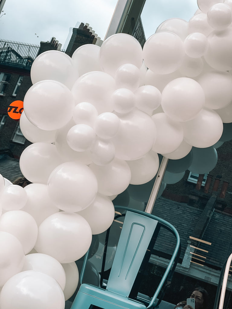 White summer party balloon garland for corporate office party decor.