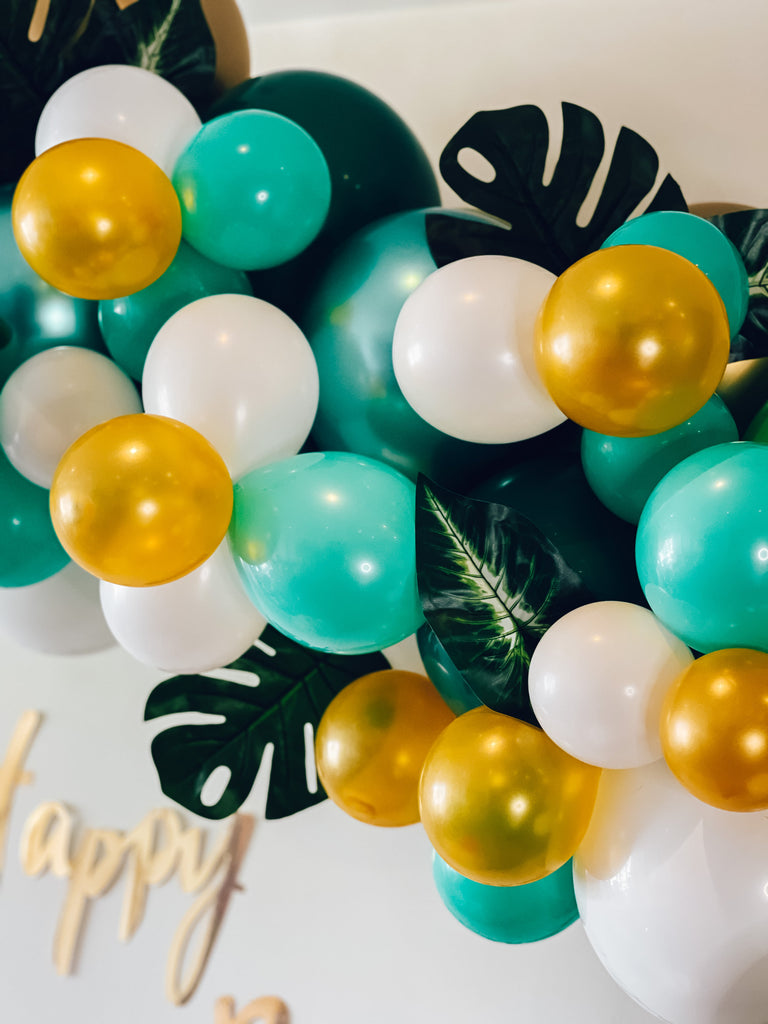 Jungle themed kids party balloon garland kit in green, yellow, white and gold balloons and birthday bunting.