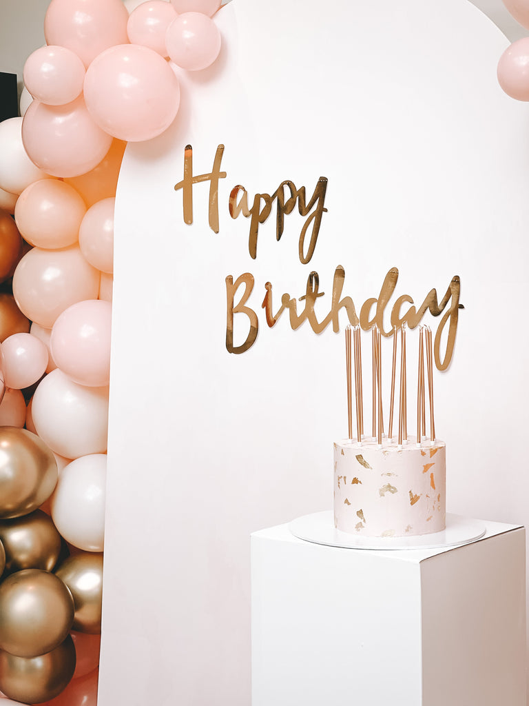 Beautiful and simple 2021 trending cake idea with pink and white birthday girl cake with gold art foils and gold long birthday candles.