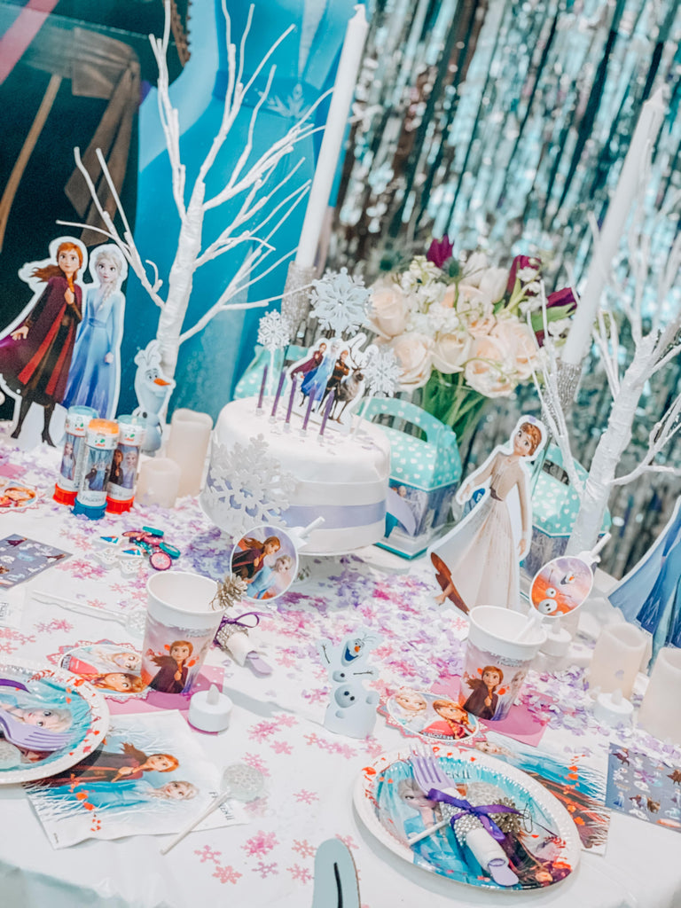 Frozen Party themed table decorations for children's birthday party with Elsa and Anna. Magical Frozen kids party themes and ideas with Frozen cake, tableware, snowflake confetti, and other frozen party supplies.