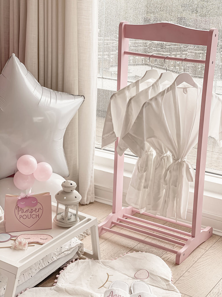 Bespoke girls spa themed sleepover slumber party personalised white silk bathrobes on pink kids clothing rail with star sleepover balloons and personalised pink spa themed party bag favours.