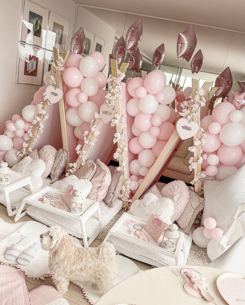 Slumber sleepover pink girls party with bespoke teepee design, balloon decorations, white tray tables, party tableware and supplies, cloud rugs and cushions with cute sleepover party puppy.