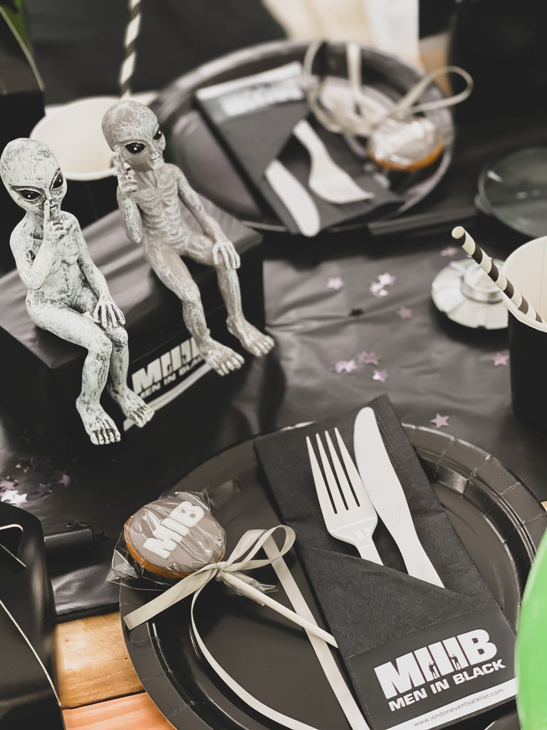 Men in Black themed birthday party table decorations and accessories. Alien themed table decor tableware and cutlery set.