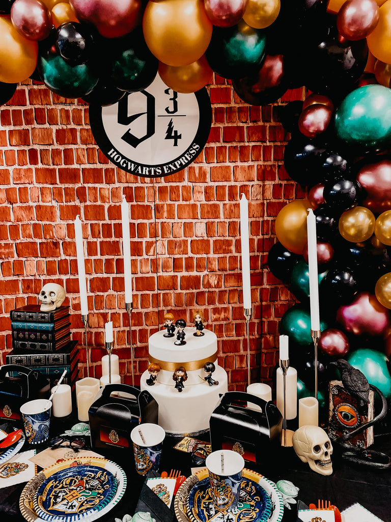Harry Potter themed kids birthday decorations and supplies for themed birthday celebration themed dessert table with horgwarts plates, candles, cups, napkins, balloons, decorations and party bags themed to Harry Potter movies and books.