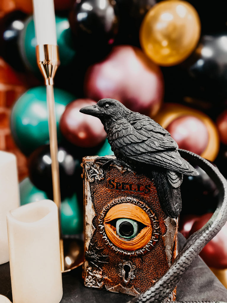 Themed Harry Potter party decorations with crow, spell book, Harry Potter invitation, balloon garland and candles to set the theme for Harry Potter themed kids birthday party.