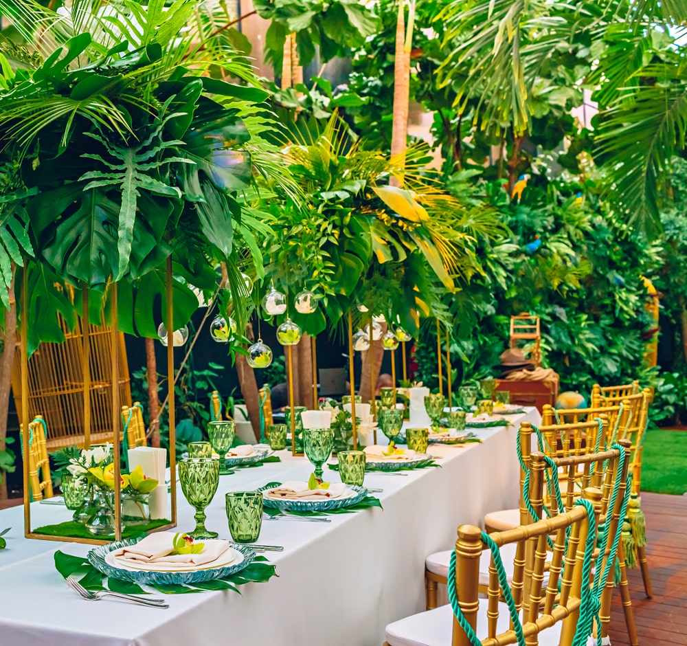 beautiful flamingo themed party tropical party table and chairs with foliage and flowers decorated party tabletop, tableware and cutlery.