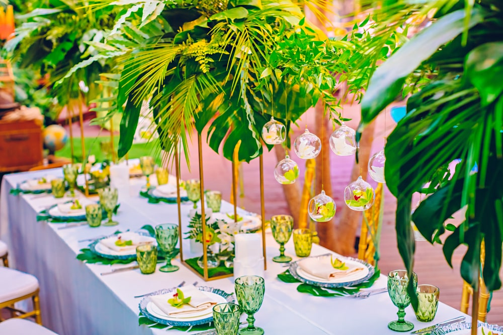 Jungle themed party table with green and yellow safari jungle themed tableware and cutlery. High quality table scatter jungle leaves table floral arrangement centrepiece.