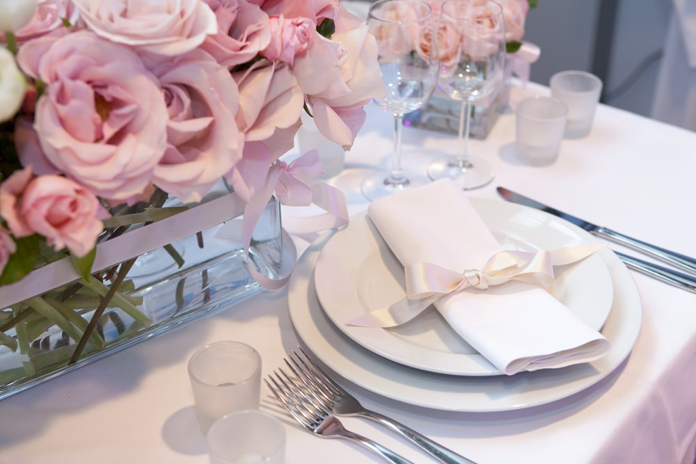 Pink and white tableware party table decor setting for baby shower and girls birthday celebrations with plates, cups, cutlery, napkins and flower arrangement bouquets for table decorations.