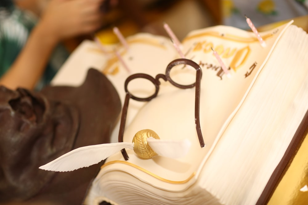 Harry Potter Themed birthday cake potion book with harry's glasses, sorting hat and a golden snitch from icing sugar and cream.