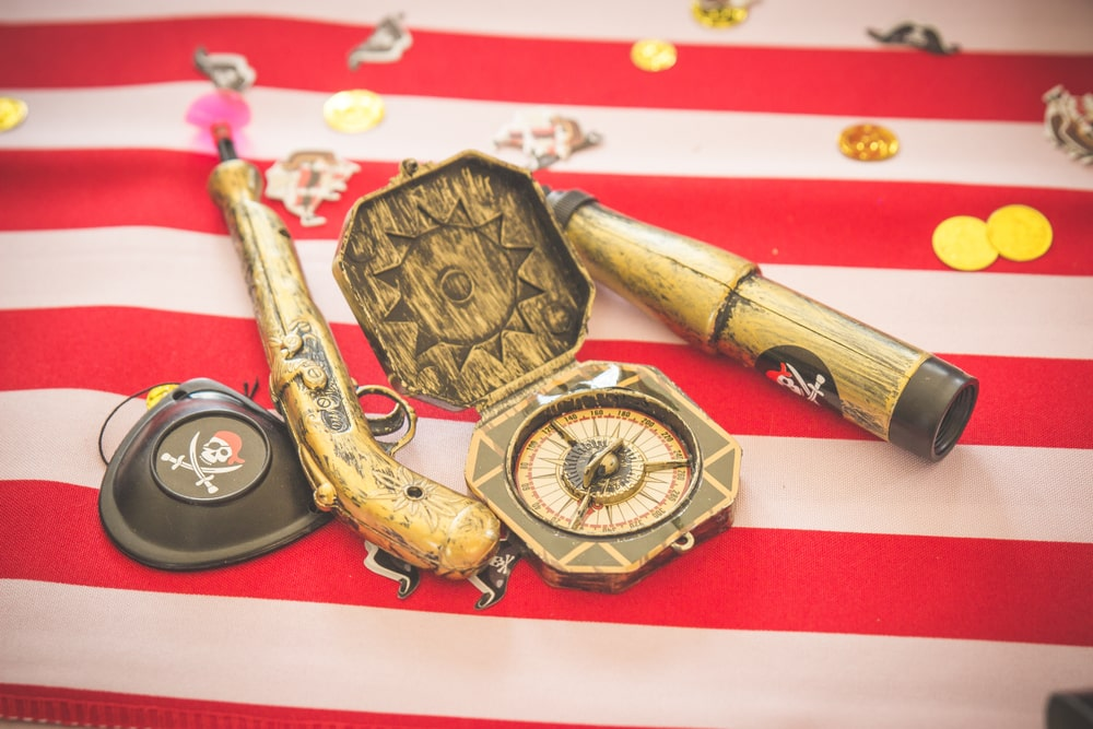 Pirate themed kids party decorations props for children's party styling like compass, guns, treasure chest, treasure maps, gold coins and pirate jewels