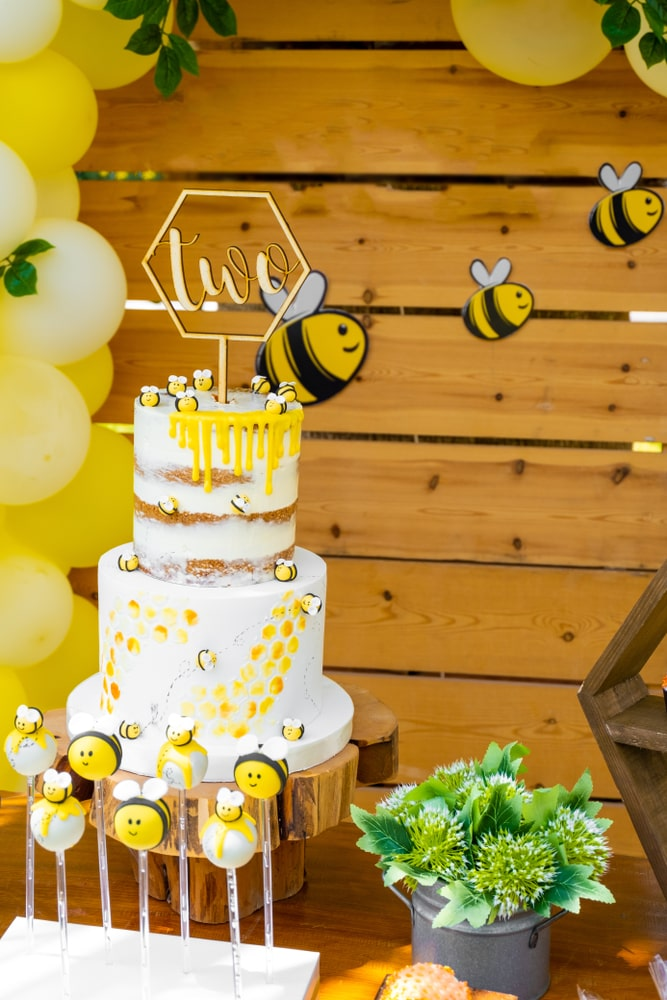 bumble bee themed white and yellow cake with bee cake pops and bee decorations on a bee party themed party backdrop and yellow balloon garland.