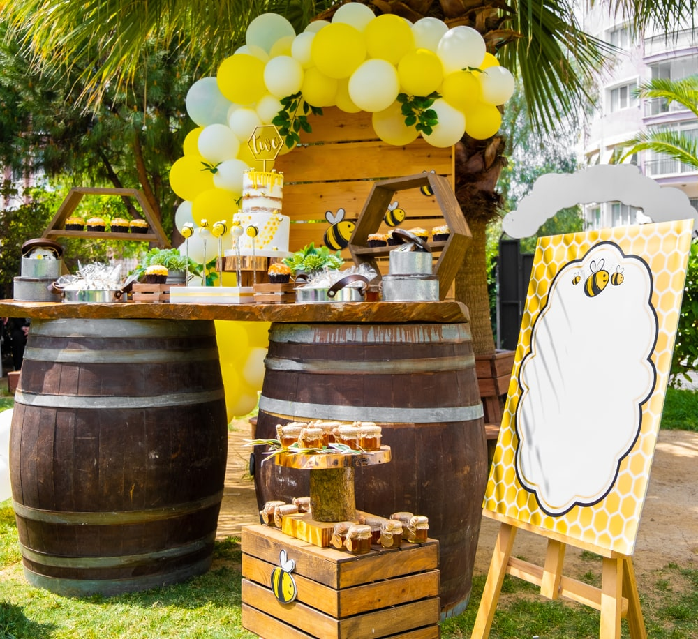 Bee party table setup with bee party decorations, dessert table, themed desserts and yellow and white balloon garland on a birthday backdrop for Bumble bee party arrangement.