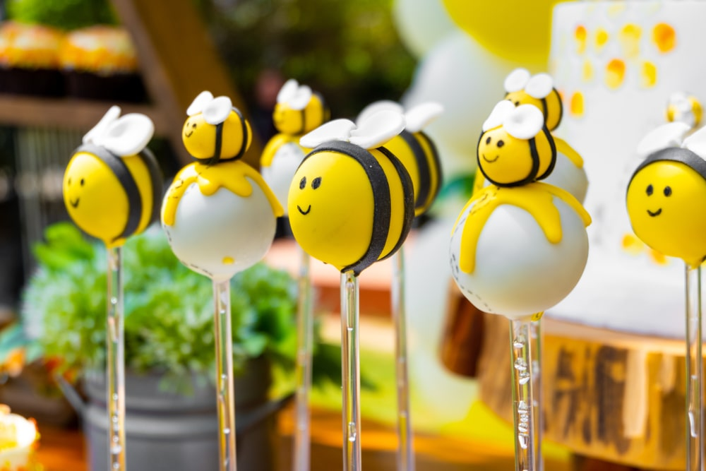 Bumble bee party dessert table with yellow black and white themed bee cake pops.
