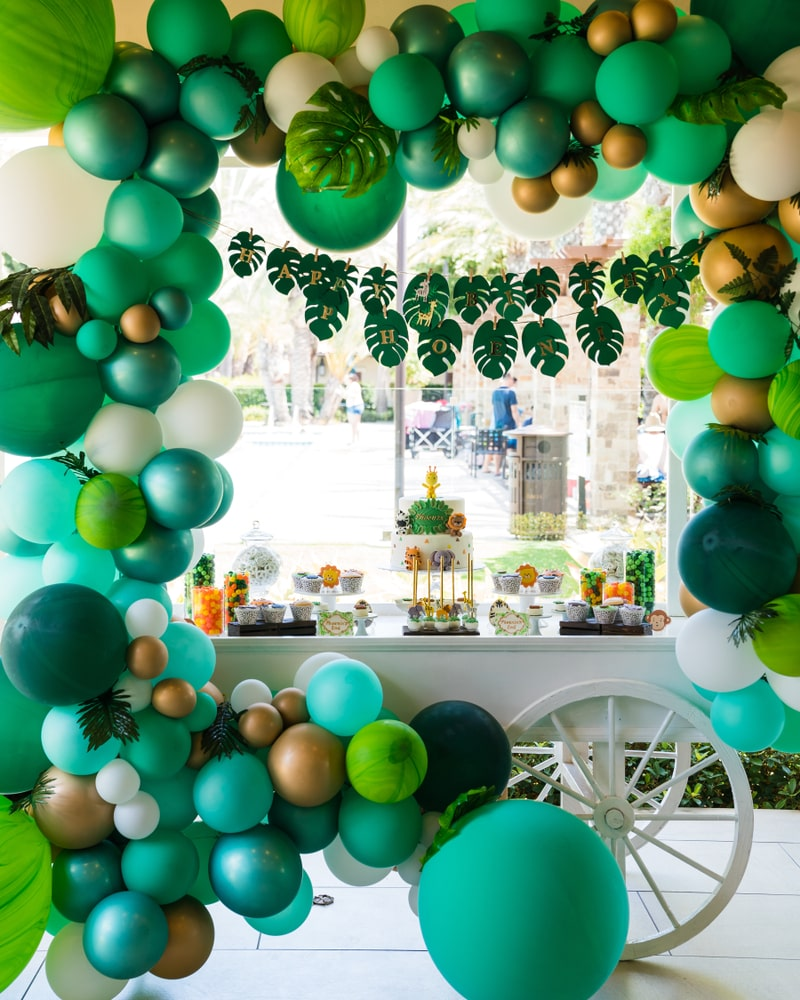 Jungle Party theme ideas for kids birthday celebration with jungle themed green and yellow balloon garland, jungle leaves bunting, jungle animal birthday cake and white dessert table cart.
