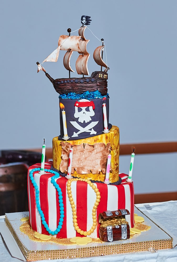 3 tier huge Pirate party cake with pirate flag, pirate ship, pirate treasure chest with gold coins and jewels.