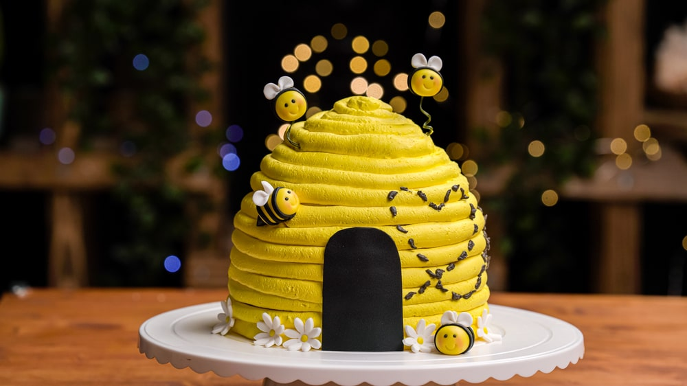 Bumble bee party bee hive yellow cake decorated with bee sugar cake topper decorations for a bee birthday party dessert table.