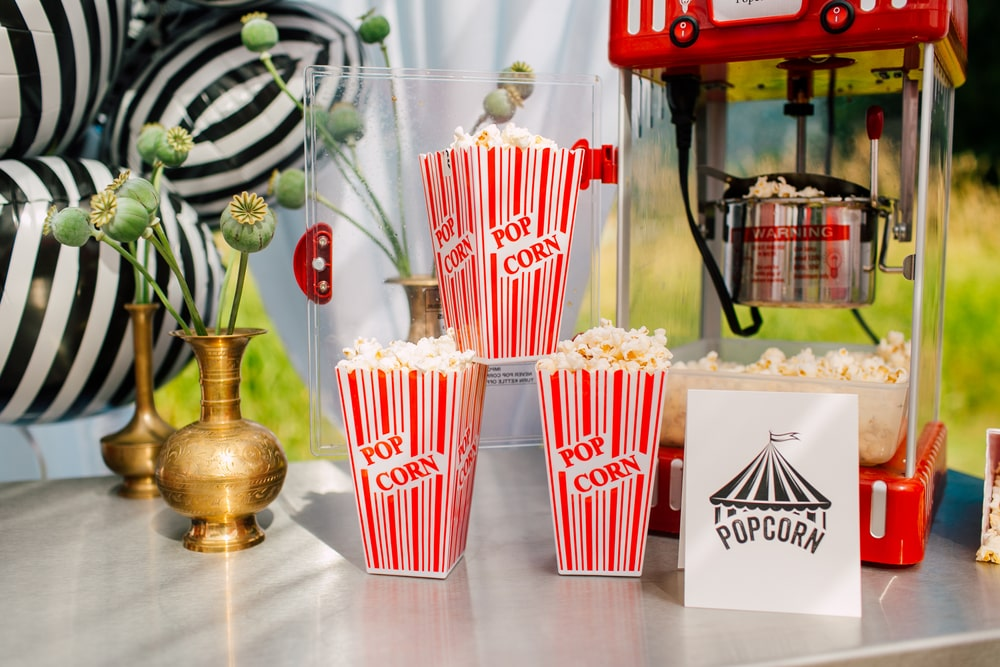Circus themed birthday kids party decor ideas with circus dessert table pop corn stand and themed circus props.